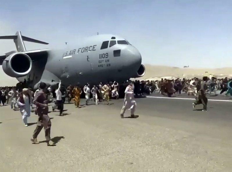 美國空軍C-17運輸機16日在喀布爾國際機場準備滑行起飛前,數百名急著想逃離當地的阿富汗人跟著移動中的飛機奔跑。美聯社