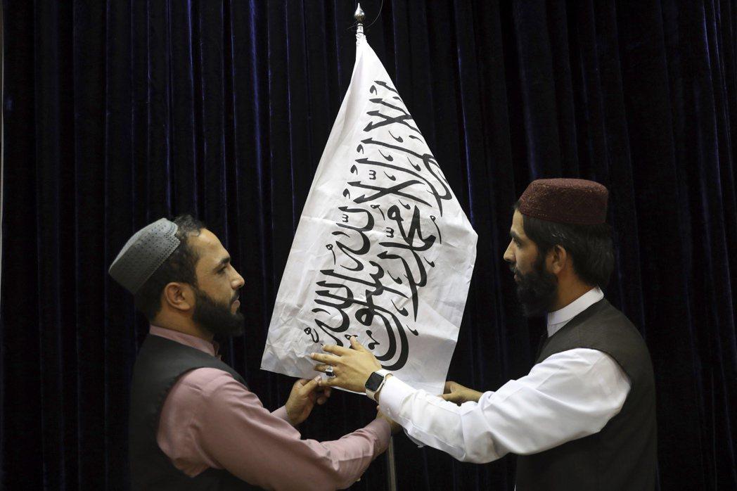 圖為塔利班成員在記者會前升起塔利班旗幟。 圖/美聯社