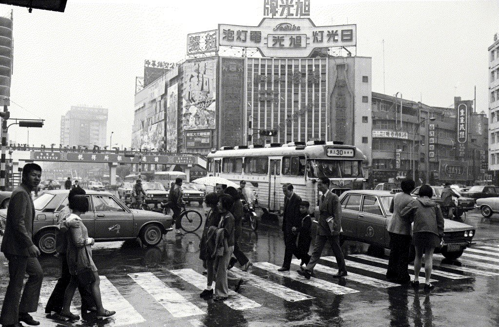第二代新聲戲院(1968–1988),院名由 「新生」改為「新聲」,與西門町的「樂聲」、 台北圓環的「國聲」合為三聲連鎖。第一代的新生和第二代的新聲在外牆的布局依稀相似,直式長立面之外,另有臨著中華路的大面積橫式立面,可切割成多塊廣告空間。圖片裡最醒目的電影宣傳是經典名片《桂河大橋》的重映廣告。 圖/聯合報系資料照