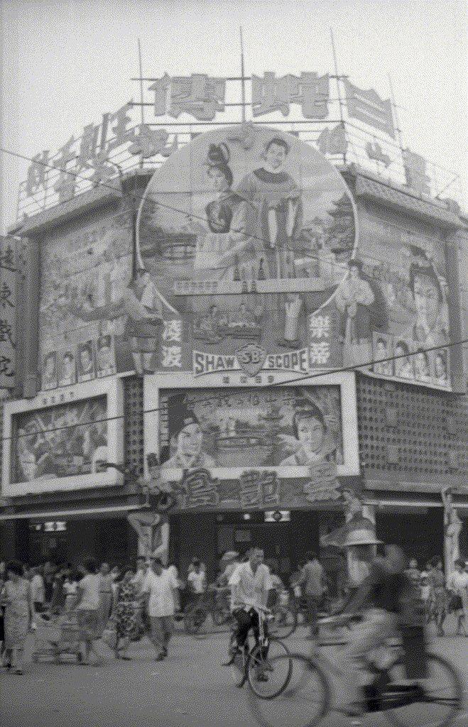 1963年5月,《梁山伯與祝英台》在遠東及中國戲院上映時的戲院外觀盛況照片。這張直式照片可以清楚看到中央大圓盤,左右兩側立面(左側是十八相送——對應到太原路;右側是樓台會,對應到平陽街),戲院屋頂的巨大霓虹燈字,中層兩個白方塊是原本預留的電影廣告,還有尚未上映的歐洲新片《黑艷鳳》立體字樣,以及左右立柱兩位艷舞女郎的木板切片。 圖/聯合報系資料照