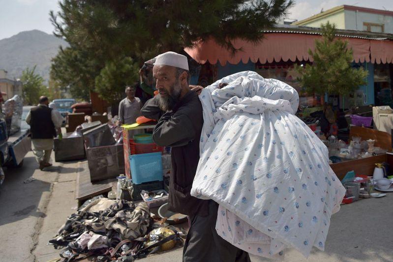 許多阿富汗人將可以立刻賣出的多餘物品背在身上,或推著搖晃的攤車到跳蚤市場販賣。法新社