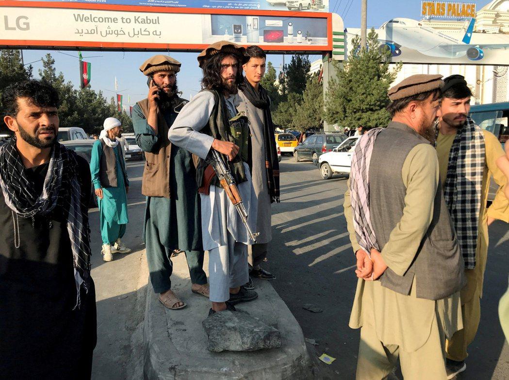 一名塔利班成員(持槍者)站在阿富汗喀布爾的哈米德卡爾扎伊國際機場外。 圖/路透社