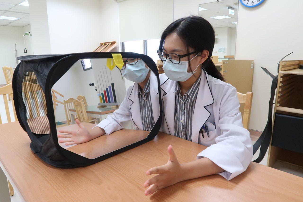 職能治療師蔡宜軒利用「鏡像治療」,改善中風患者偏癱的情況。 圖/南基醫院提供
