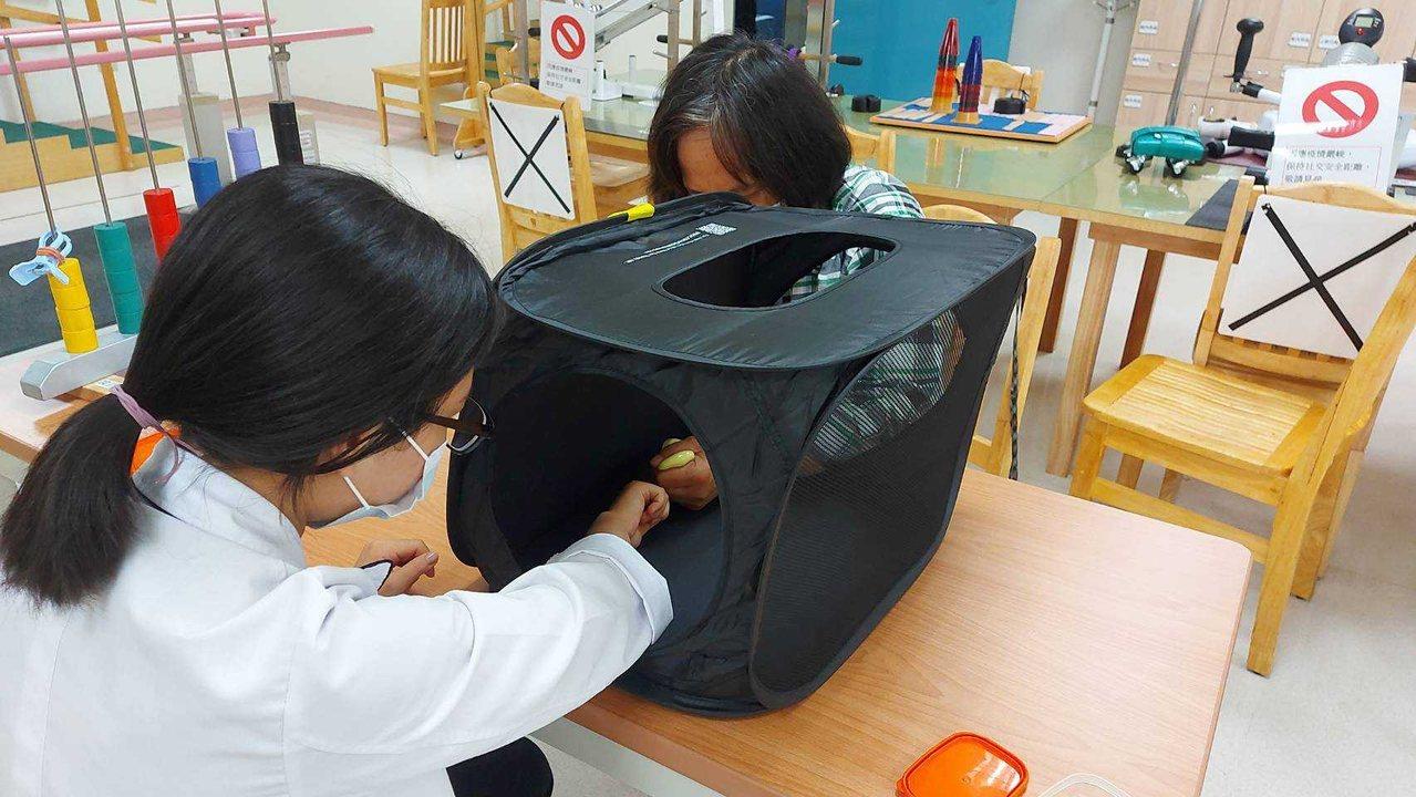 職能治療師蔡宜軒(左)利用「鏡像治療」,讓中風患者慢慢恢復知覺功能。 圖/南基醫...
