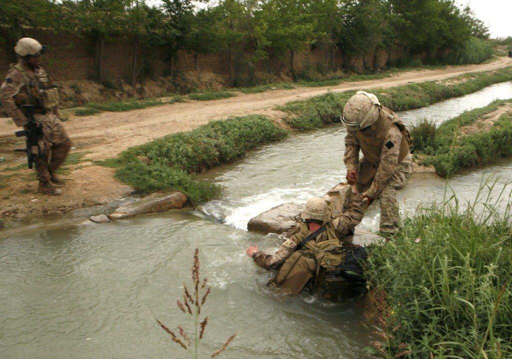 赫爾曼德省激戰區,一名阿富汗翻譯,正在幫忙落水的美軍起身。 圖/路透社