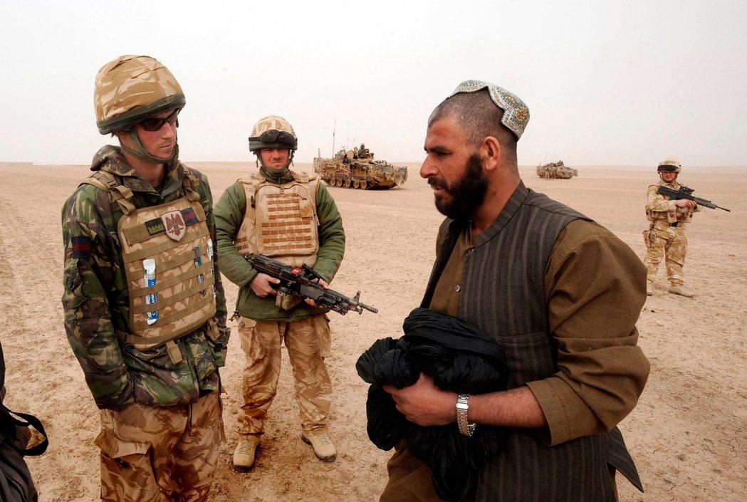 2015年,在阿富汗隨軍翻譯(沒被拍到)的幫助下,英國王子哈利與一名阿富汗人交談...