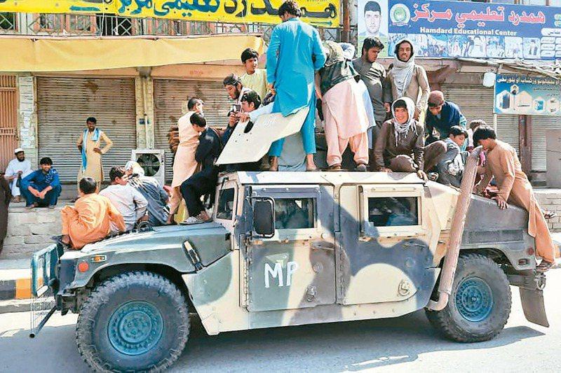 阿富汗政府軍潰敗速度驚人。圖為阿富汗拉格曼省,神學士成員和當地民眾坐著一輛從政府軍手上繳獲的悍馬車。法新社