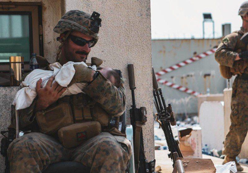 大兵將嬰兒抱在懷裡安撫、面露慈笑。 圖/U.S. Marine Corps