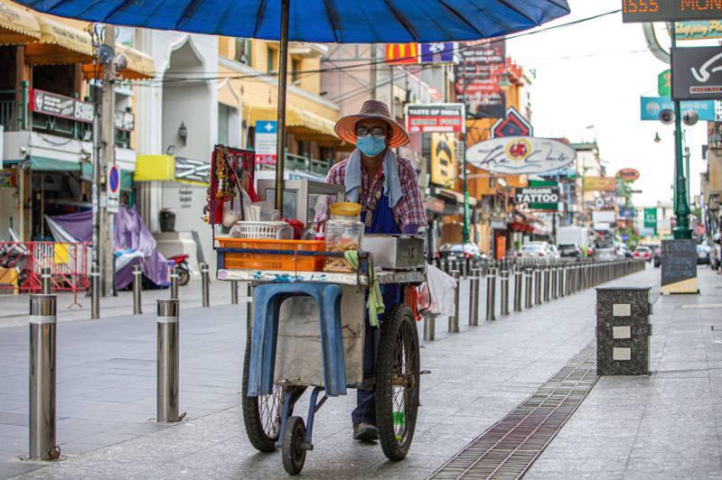 泰國累計新冠確診病例數破百萬,圖為曼谷一名戴口罩的商販推車走過考山路。新華社