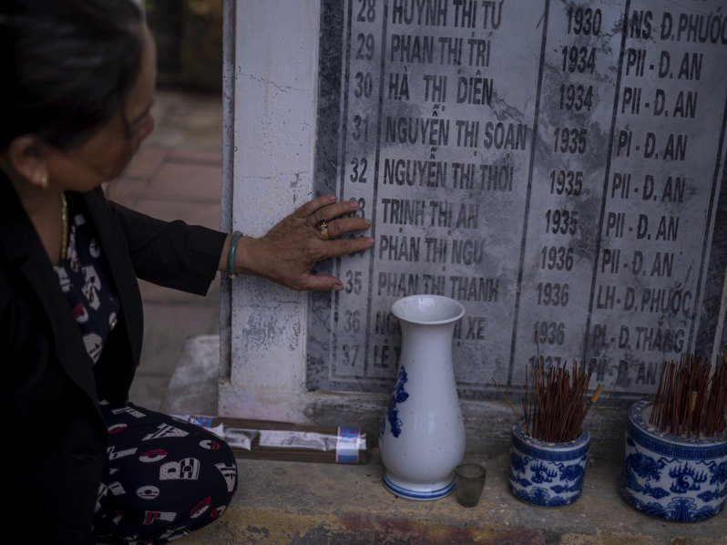 越南人阮氏清是越戰時期豐一村及豐二村屠殺事件倖存者,圖為她在廣南省一處紀念碑指著罹難人姓名。圖/取自紐約時報