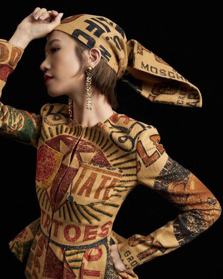 Lulu身穿MOSCHINO秋冬系列,以復古印花麻布袋剪裁為喇叭袖、裙撐和蝴蝶結...