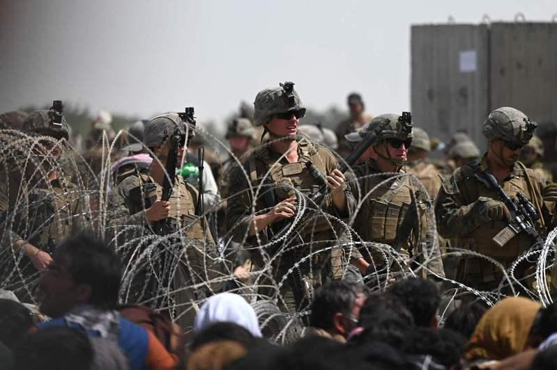 美國官兵20日在阿富汗首都喀布爾機場軍事區附近蛇籠駐守,現場聚集了想逃出阿富汗的民眾。法新社