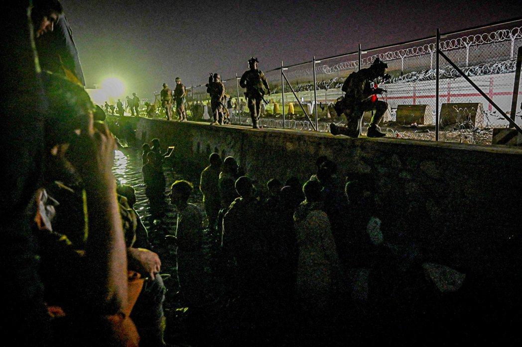 圖為8月22日深夜,阿富汗人在KBL機場的外國軍事控制區外、浸身在運河裡等候,希...