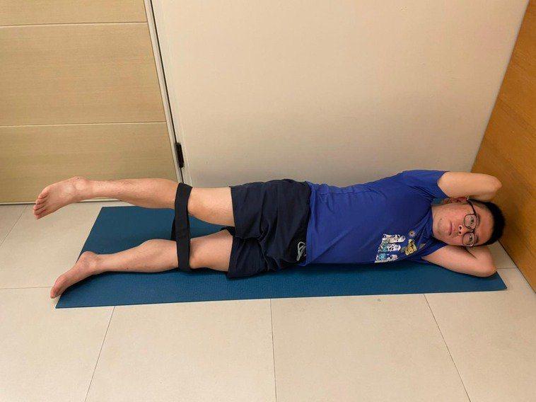 側躺,腿部繞一圈彈力帶,疼痛側髖部在上。 圖/新北市立土城醫院復健科主治醫師陳渝...