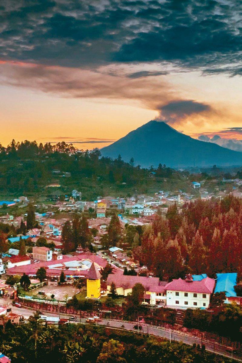 印尼北蘇門答臘的西納彭火山廿七日噴發濃煙,正是夕陽西下時分。(法新社)