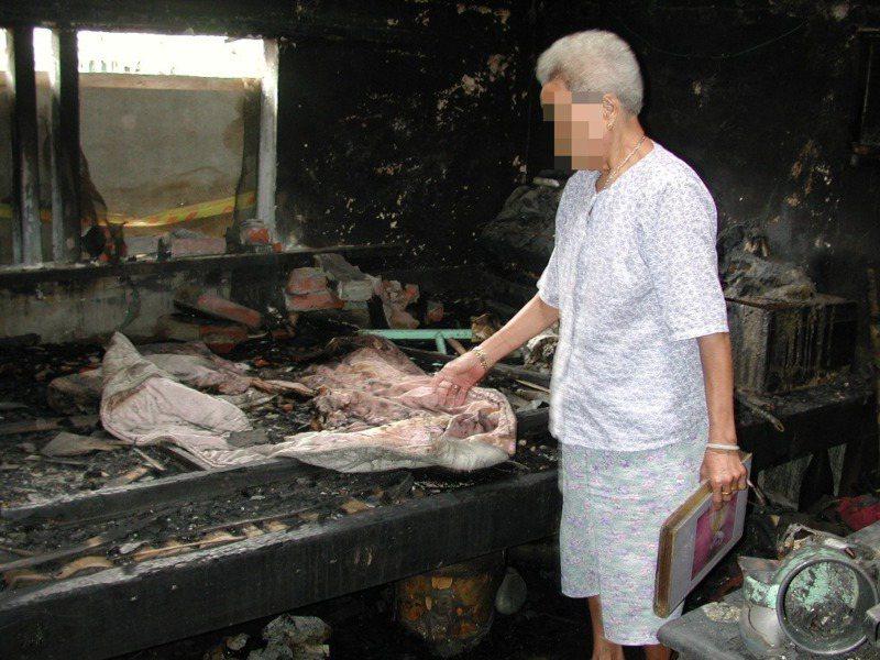 蘇姓老婦在命案現場摸著女兒生前蓋的被子,痛斥林嫌縱火殺妻,死不足惜。圖/聯合報系資料照片