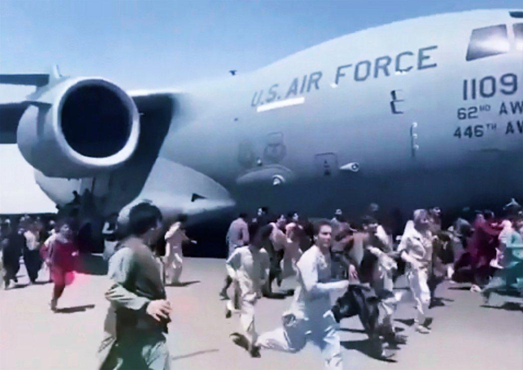 圖為喀布爾淪陷後,闖入機場跑道、追逐美軍撤僑C-17運輸機的阿富汗人。 圖/...