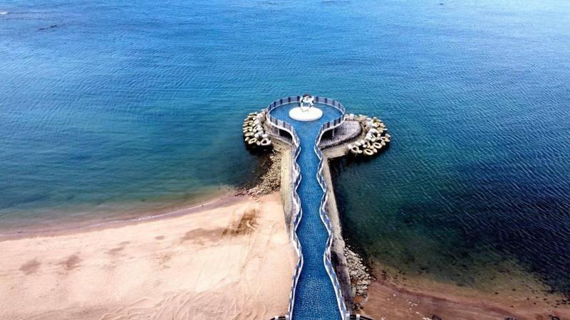 空拍視角俯瞰三芝淺水灣芝蘭公園的「望海平台」,遼闊藍海與海上平台美不勝收圖/新北市政府提供