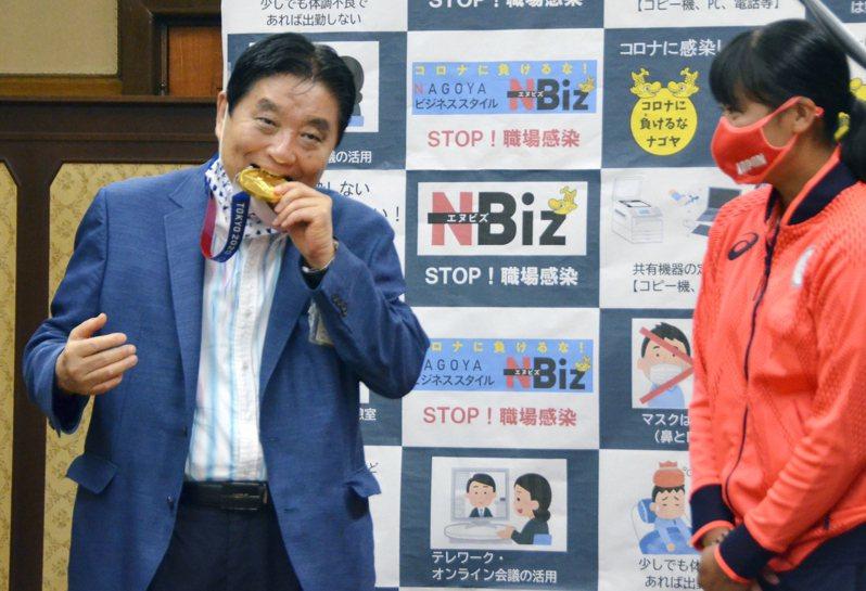 名古屋市長河村隆之(左)接見東京奧運奪下金牌的日本女壘隊選手後藤希友(右)時,突然拉下口罩,大口咬後藤的東奧金牌引發爭議。圖/美聯社資料照