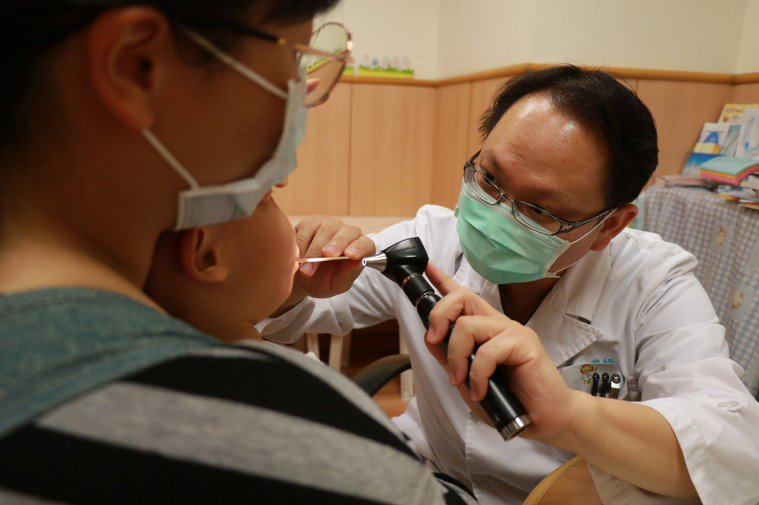 台中慈濟醫院醫師李宇正醫師(右)看診,檢查小朋友口咽。圖/台中慈濟醫院提供