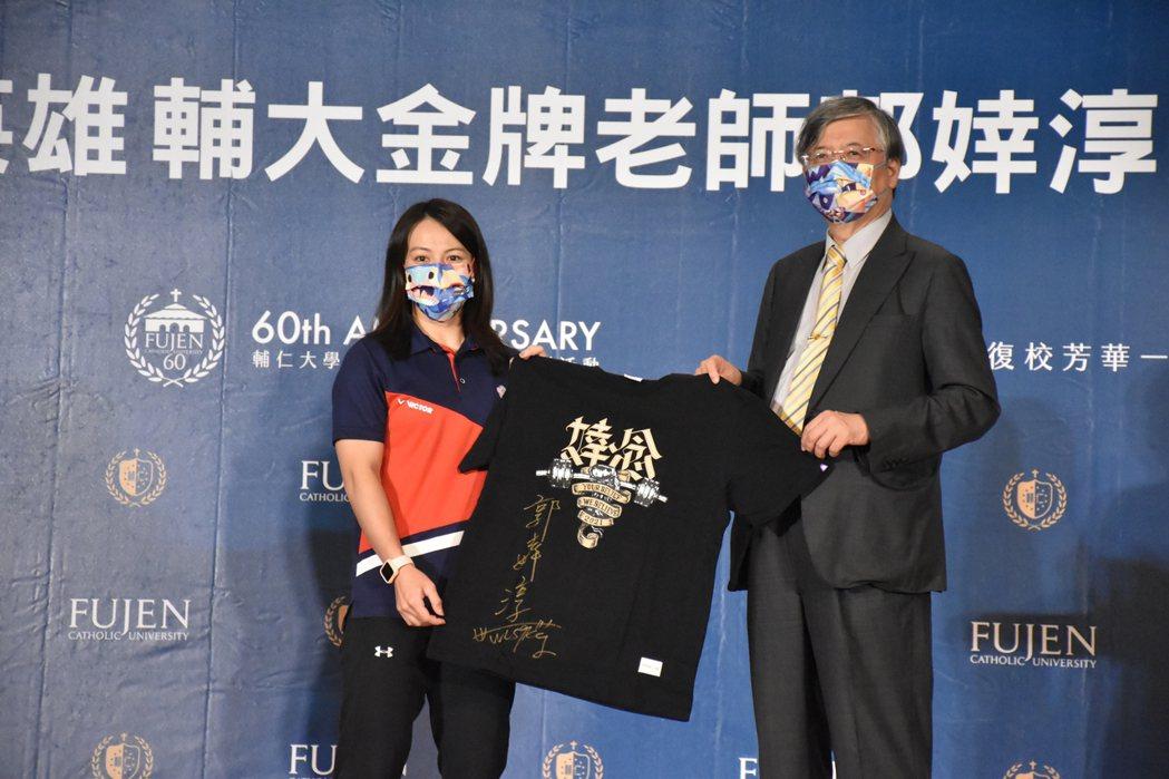 舉重選手郭婞淳(左)致贈簽名T恤衫給輔大校長江漢聲。記者江婉儀/攝影