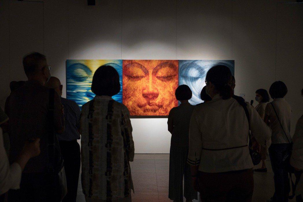 「量子」是科學名詞,「臉書」則是近年崛起的網路社群,二者的結合在張振宇的彩筆下形成一張張菩薩面容。整幅畫就是額頭至下頷的一張臉,其他身體部分儘量省略。菩薩的眼簾下垂、微笑、慈悲祥和地俯視眾生,視覺上令人震撼。圖為「張振宇:當代佛教藝術」展覽一隅。 圖/名山藝術授權提供