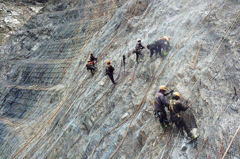 南橫公路東段142.3公里處埡口大崩塌,一群工程人員化身蜘蛛人,繫上安全索在近乎垂直的峭壁上進行邊坡整治作業。記者劉學聖/攝影