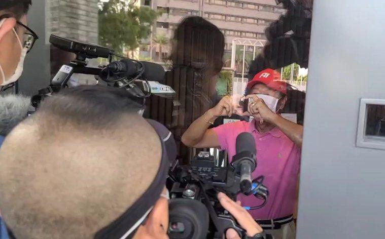 鴻海創辦人郭台銘結束隔離,上午從防疫飯店離開。他穿著粉紅色POLO杉,隔著玻璃向...
