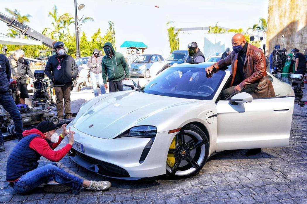 巨石強森根本塞不進Porsche Taycan。 摘自CarBuzz.com