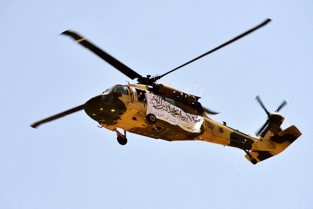 撒紙花慶祝塔利班大勝的直升機。 圖/法新社