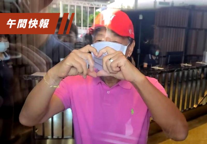 鴻海創辦人郭台銘結束隔離,上午從防疫飯店離開。他穿著粉紅色POLO杉,隔著玻璃向媒體問好比愛心手勢。記者楊凱竣/攝影