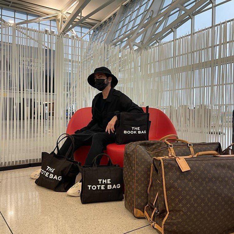 Marc Jacobs機場時尚不忘置入自家托特包,還有搶眼的LV旅行袋。圖/取自...