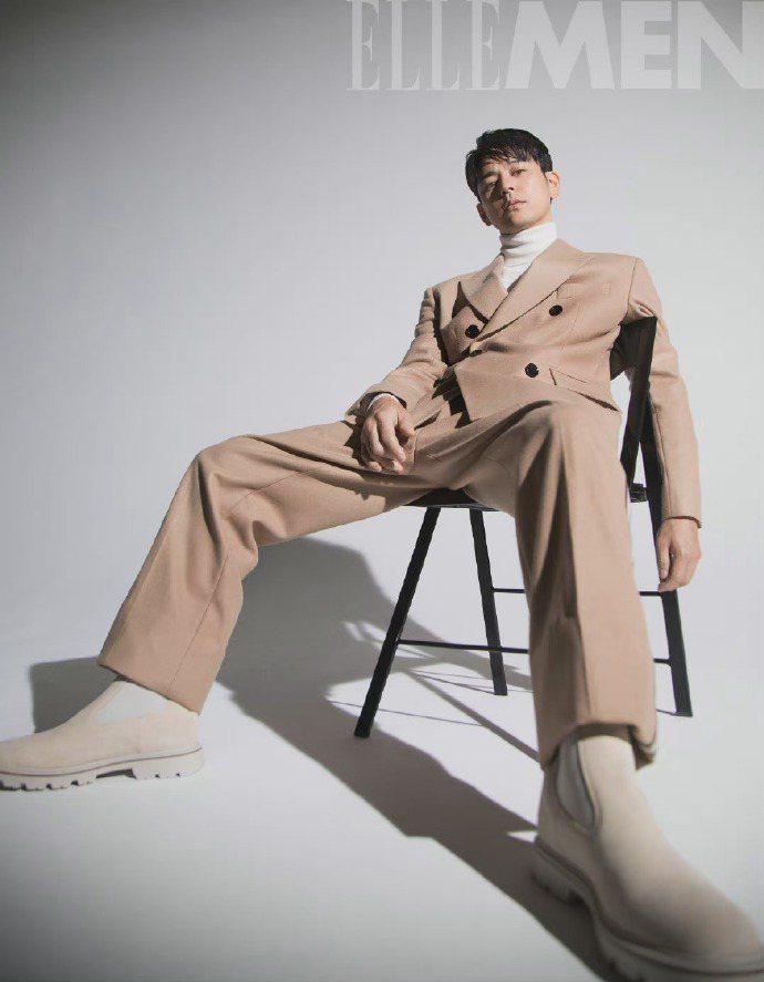 妻夫木聰身穿BOSS雙排釦西裝外套、白色高領毛衣、駝色西褲,搭配米色切爾西靴款。...
