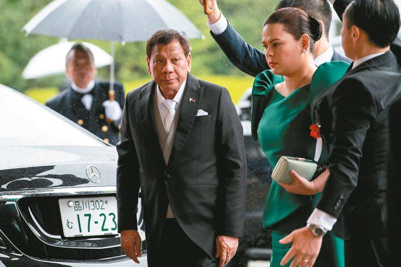 菲律賓總統杜特蒂(左)出席重大場合都會帶上女兒薩拉(綠衣者),傳承意味濃厚。(路透)