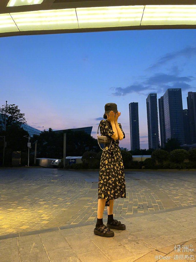 迪麗熱巴穿著GANNI碎花洋裝,搭配LV包款、eytys鞋履,用手遮臉相當可愛。...
