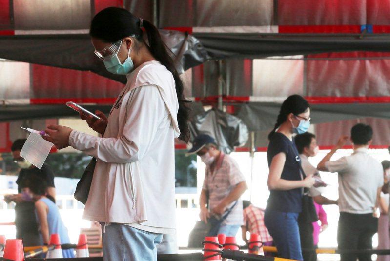 新冠病毒變異株,台灣的防疫和苗政策不但決策緩慢,指揮中心甚至被質疑「小圈圈決策」,圖為新北某大樓發生群聚,民眾湧入附近快篩站。圖/聯合報系資料照片