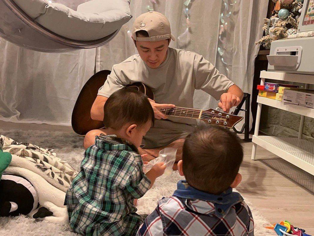 李國毅顧兩娃,準備彈吉他給小孩聽。圖/摘自臉書