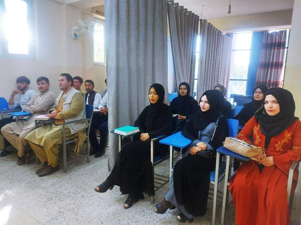 9月6日,隔著布簾區分性別上課的大學生們。 圖/路透社