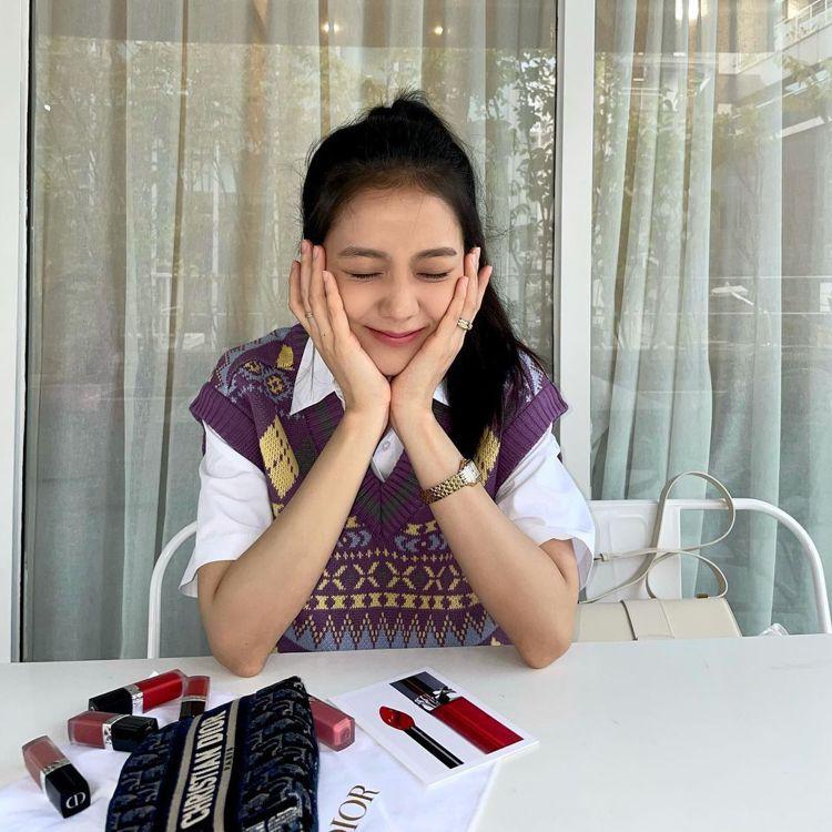 Jisoo以短袖襯衫搭配紫色的民俗風圖騰針織長背心,露出一截內裡的襯衫打造層次感...