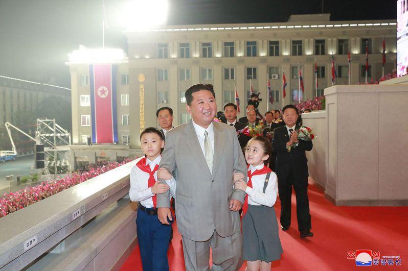 北韓領導人金正恩9日穿著灰色西裝,繫閃亮的白色領帶在建政73周年閱兵式亮相,雙手分別被一名男童和女童牽著。法新社