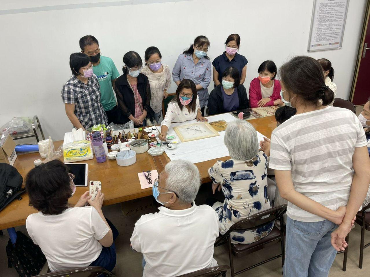 於課堂中示範工筆畫,學員們都很專注學習(拿畫筆者為邱素美)。  圖/邱素美