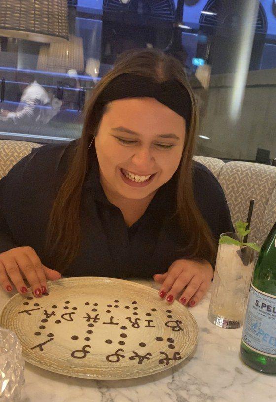 餐廳送上用巧克力寫成的點字「生日快樂」,讓視障女性碰觸。圖/取自tiktok@natbysight