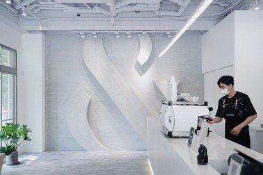FOMO COFFEE DaZhi挑高「&」符號占據整面灰牆,低調融入空間。 圖/沈佩臻攝影