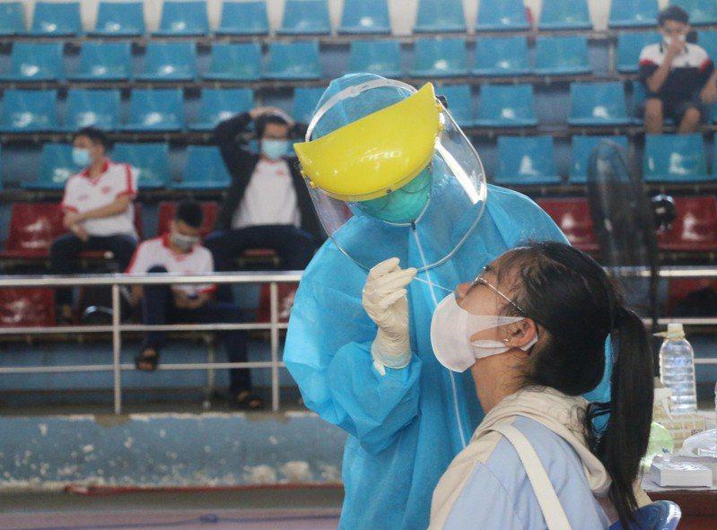 圖為越南一名中學生參加開學典禮前接受核酸檢測。新華社