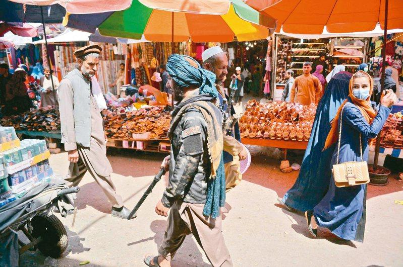 持槍的神學士民兵日前行經阿富汗喀布爾一處市場,一名女子回頭看了一眼。法新社