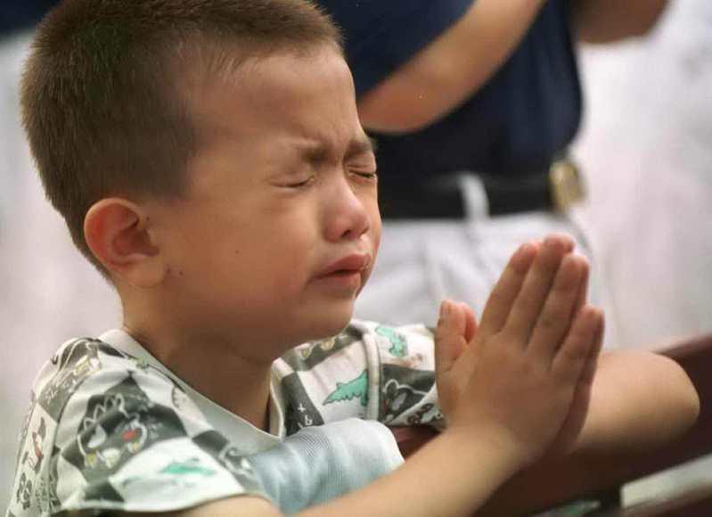 921大地震中南投中寮永平村一名小朋友失去了爸爸,淚流滿面雙手合十為震災去世的父親祈禱。圖/聯合報系資料照片