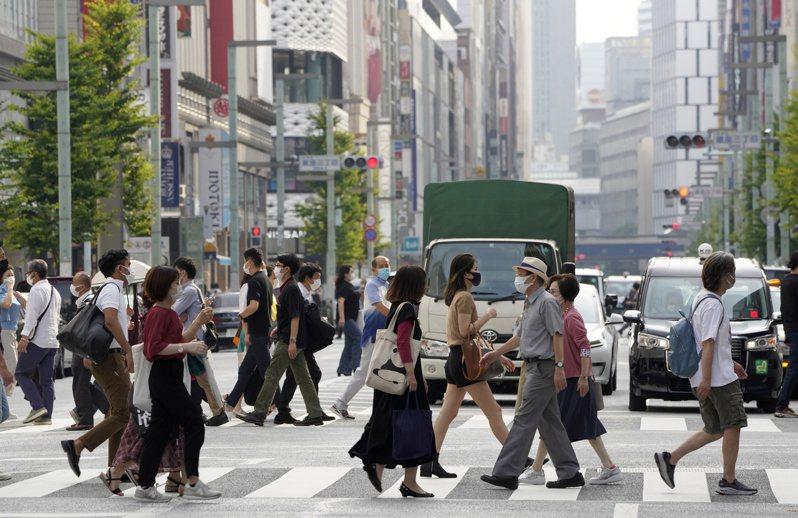 日本東京出現首例入住防疫旅館療養的新冠患者死亡案例。圖為東京行人。歐新社