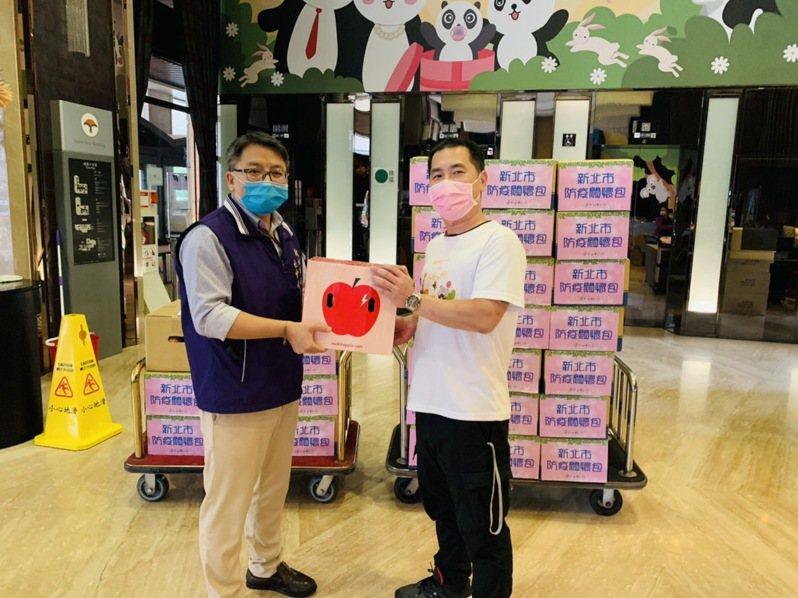新北社會局專委黃逢明(左)送物資關懷包及蘋果到深坑檢疫中心,慰問被隔離檢疫的民眾。圖/新北社會局提供