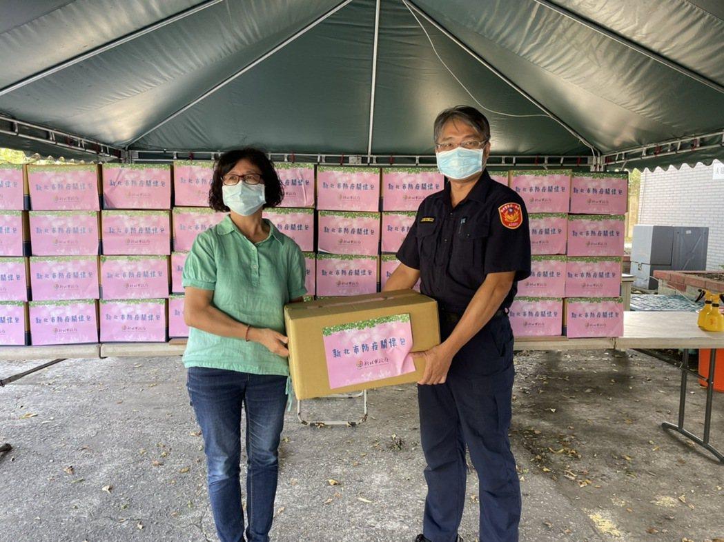 新北社會局副局長許秀能(左)攜帶內含小蘋果的物資關懷包到蘭陽檢疫所,慰問被隔離檢...