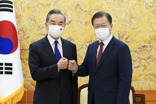 大陸國務委員兼外長王毅(左)今會見南韓總統文在寅(右)。圖/大陸外交部網站